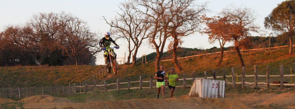 deux coureurs à coté d'une moto en plein saut